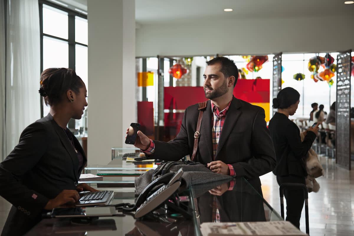 携帯電話について店員に尋ねている男性。