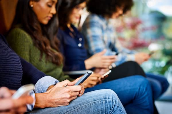 Young professionals sitting using mobile devices