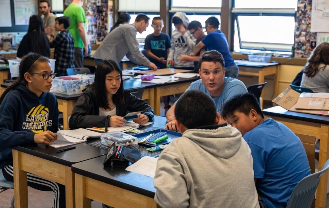 Um voluntário do Salesforce trabalhando com alunos do ensino médio na sala de aula.