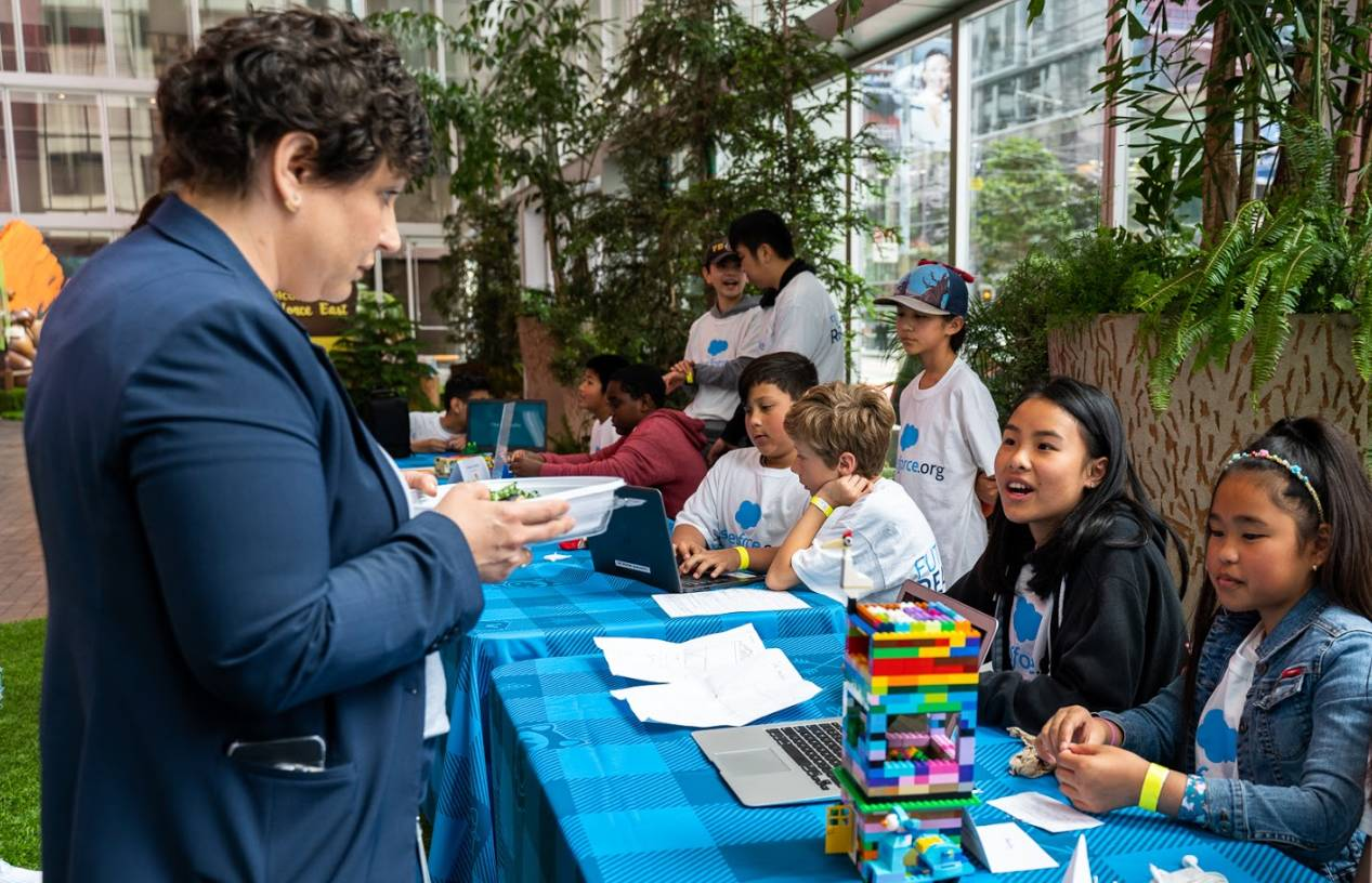 A volunteer and students gathered at Salesforce's San Francisco Bay Area Maker Faire.