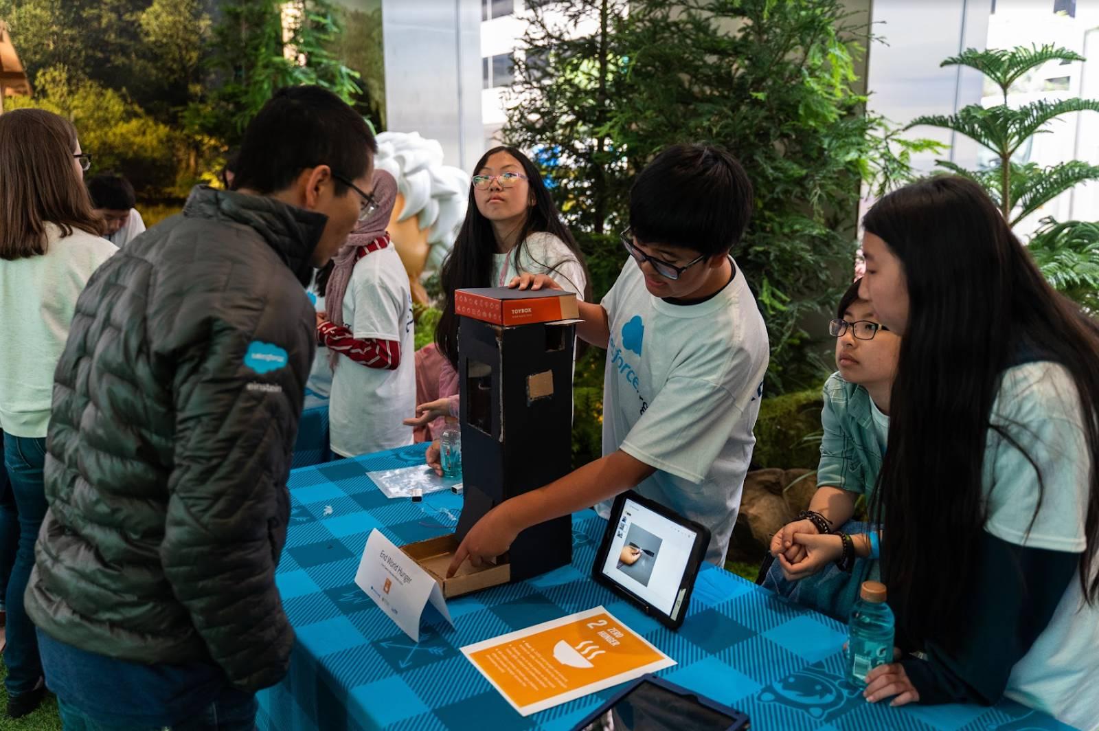 Alunos apresentando seu protótipo em uma Maker Faire da Salesforce realizada na área da baía de São Francisco