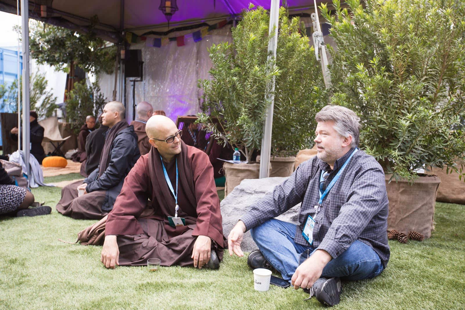 A monk from Plum Valley helps an attendee through a meditation.