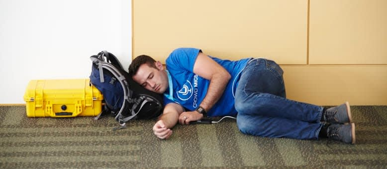 Person reclining against a wall, head resting on a backpack.