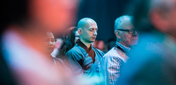 In the middle of a large audience, someone is taking in a moment of mindfulness.