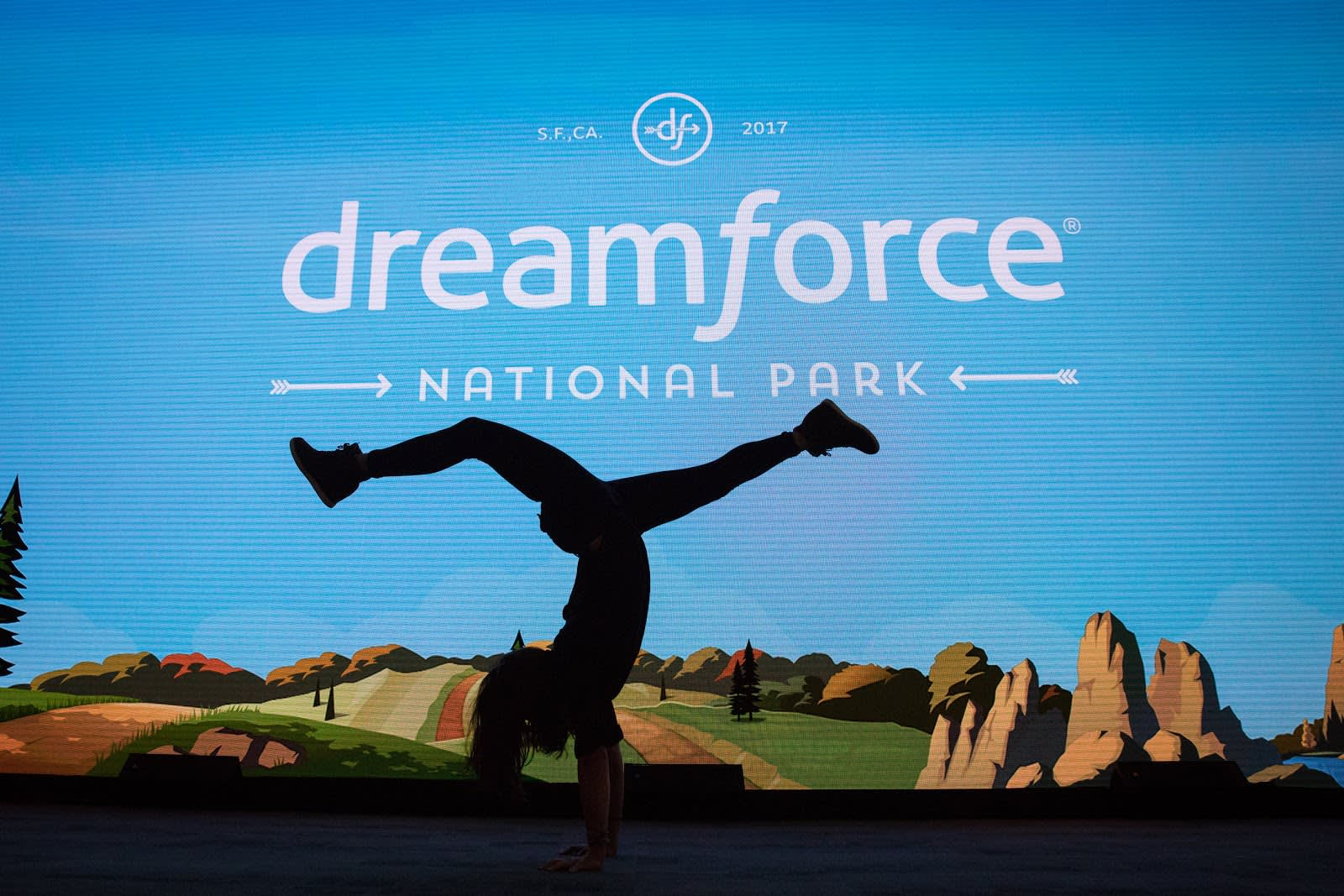 An attendee doing a handstand in front of a illuminated screen.