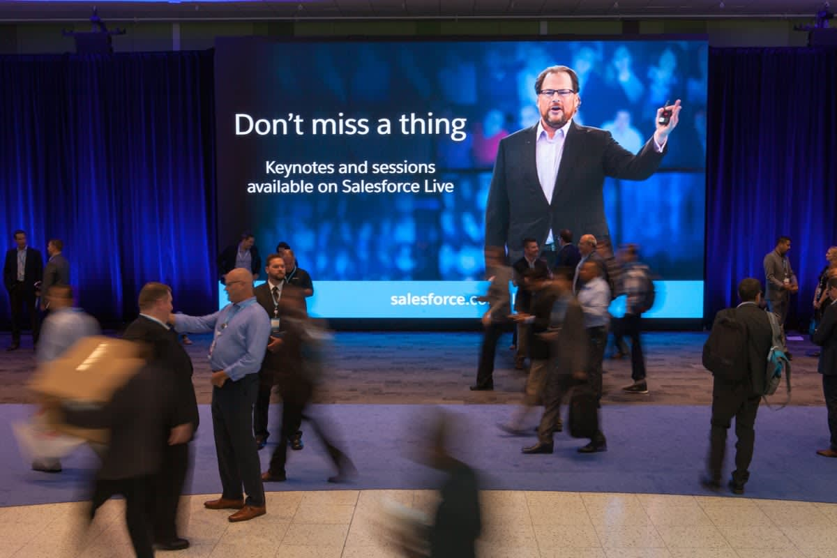 Photo of a huge screen displaying Marc Benioff as people pass by.