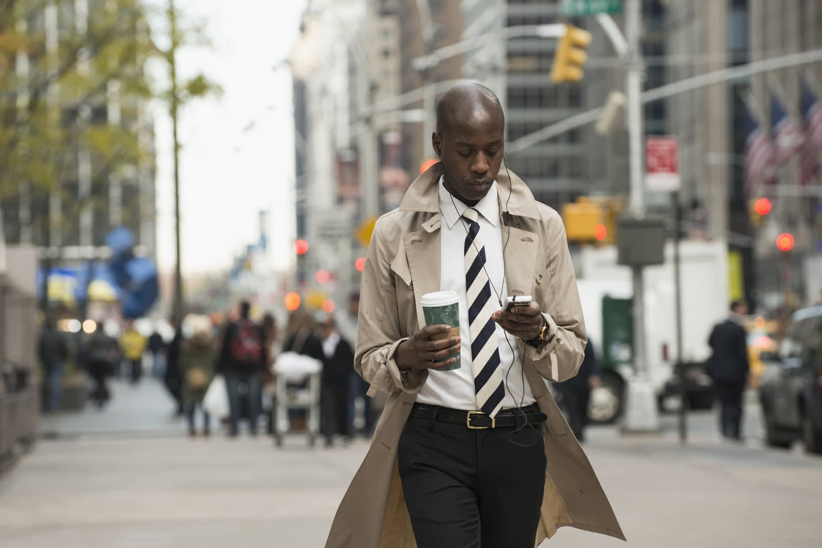 [Businessman using cell phone on city street]
