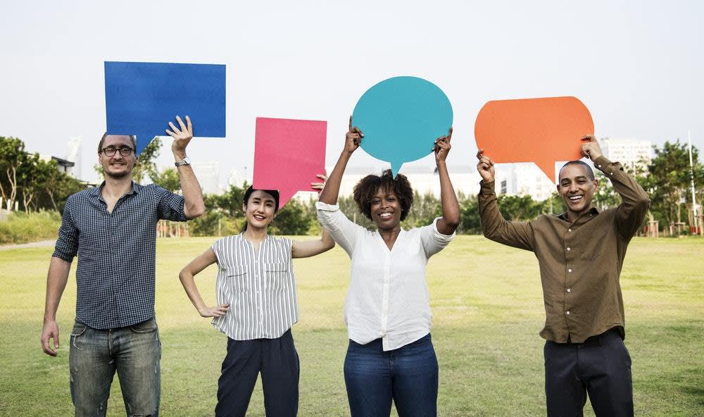 A diverse group of people stand smiling while holding speech bubbles in the air