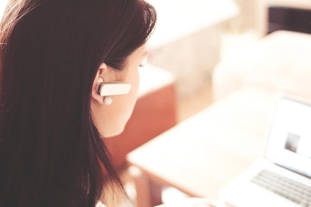 Vor einem Laptop sitzende Frau mit einem Bluetooth-Ohrtelefon.