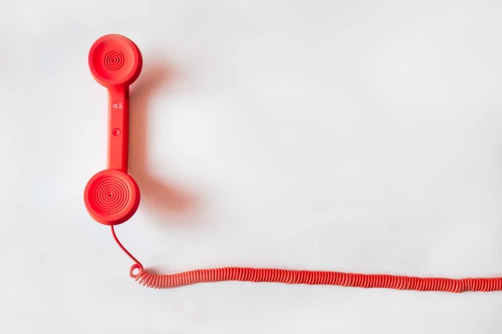 Ein rotes Telefon vor weißem Hintergrund.