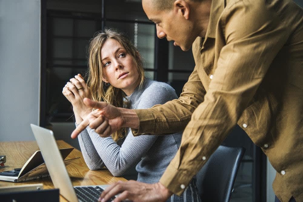 Un hombre posicionado por encima de una mujer en una configuración de oficina.