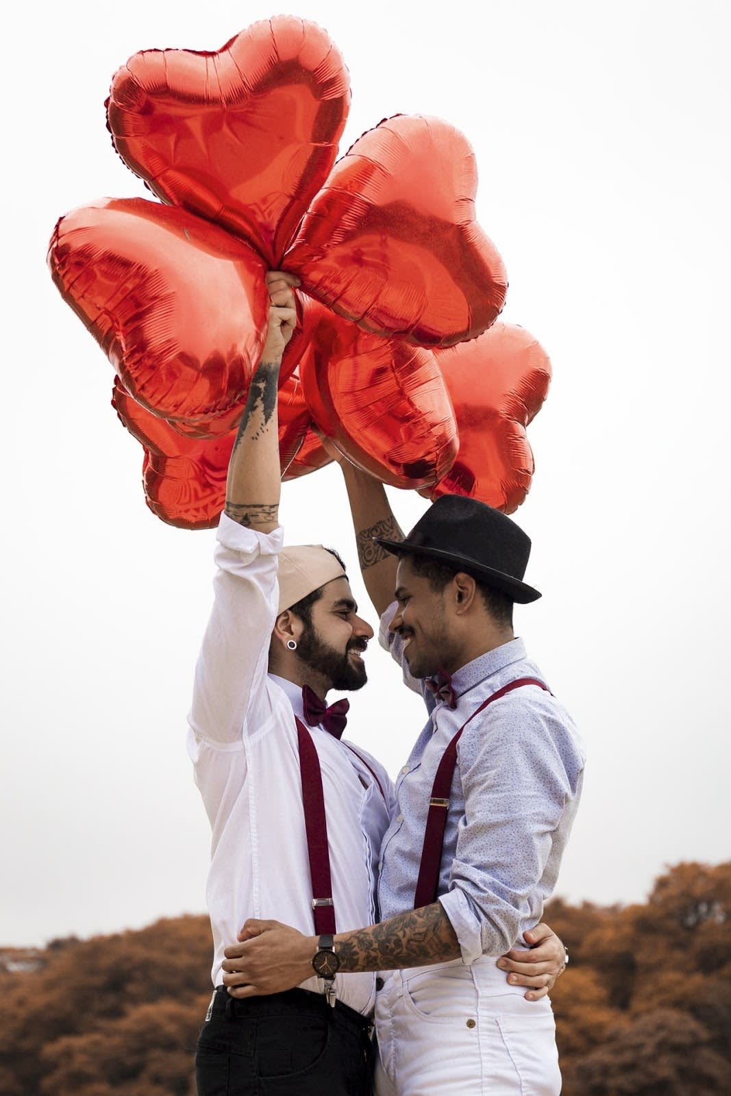 A photo of an LGBTQ couple looking lovingly into each others eyes, while holding heart balloons.