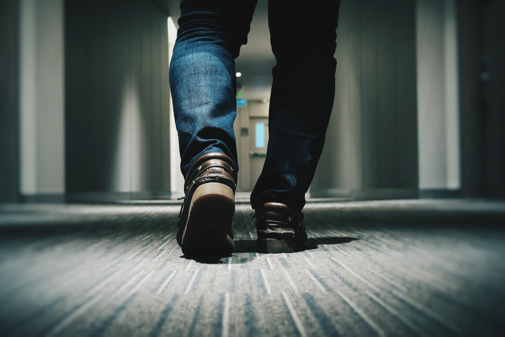 Photo of legs walking down a hall