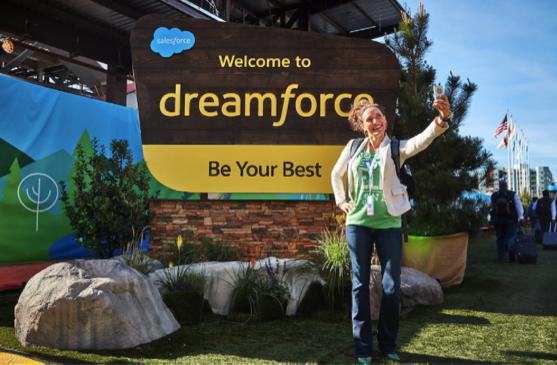 大きな Dreamforce の看板の横で自撮りをする女性。