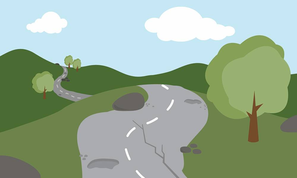 A bumpy road with rocks, holes, and cracks.