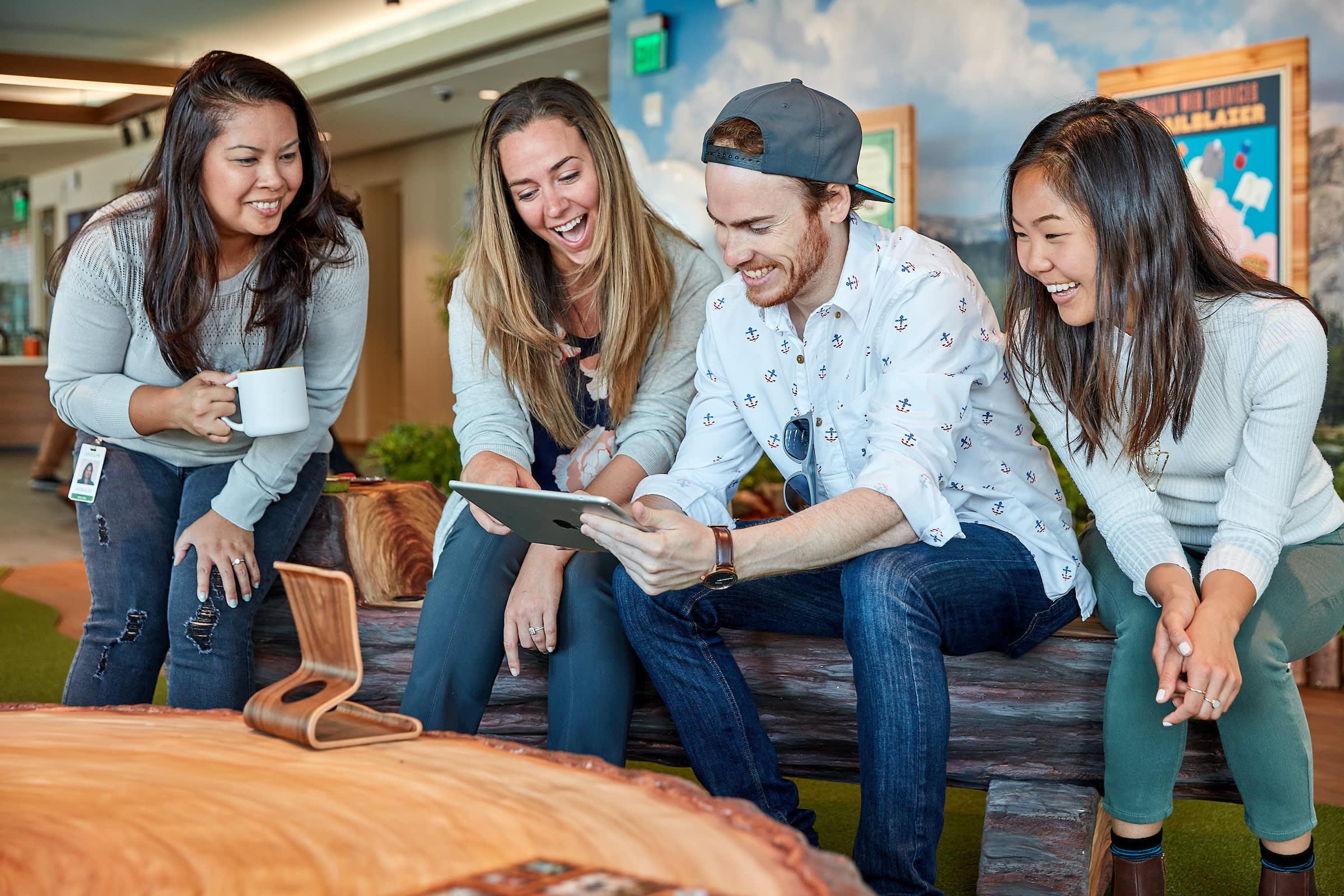 iPad を囲んで交流する、楽しげな Salesforce 従業員の画像
