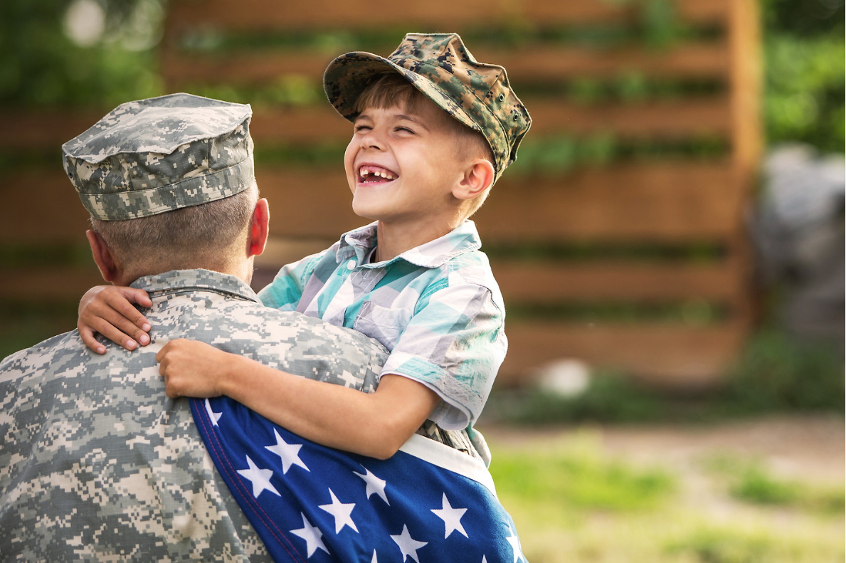 A child hugging a veteran with the American flag.