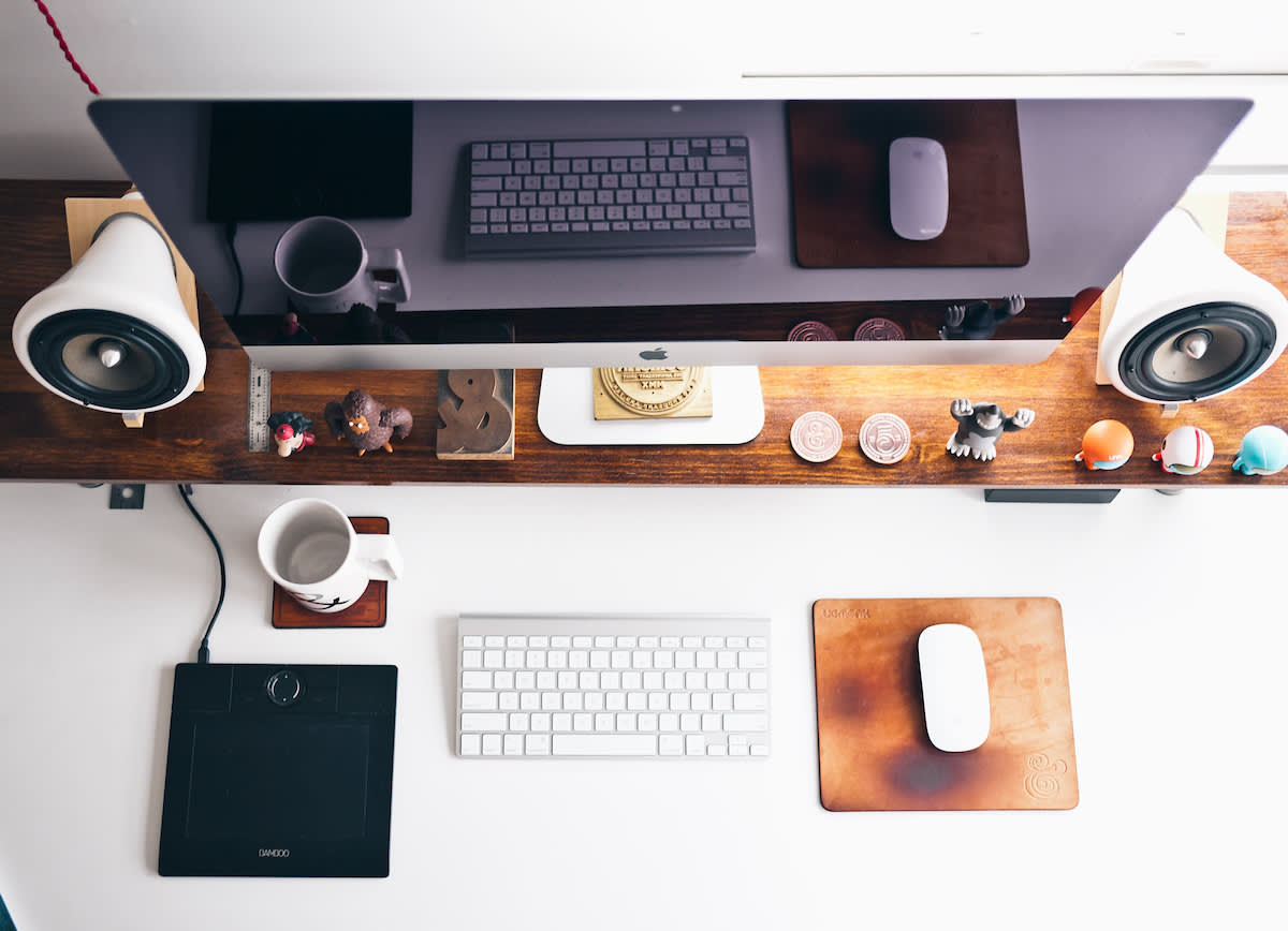A Mac screen, keyboard, and mouse on a desk with knickknacks.