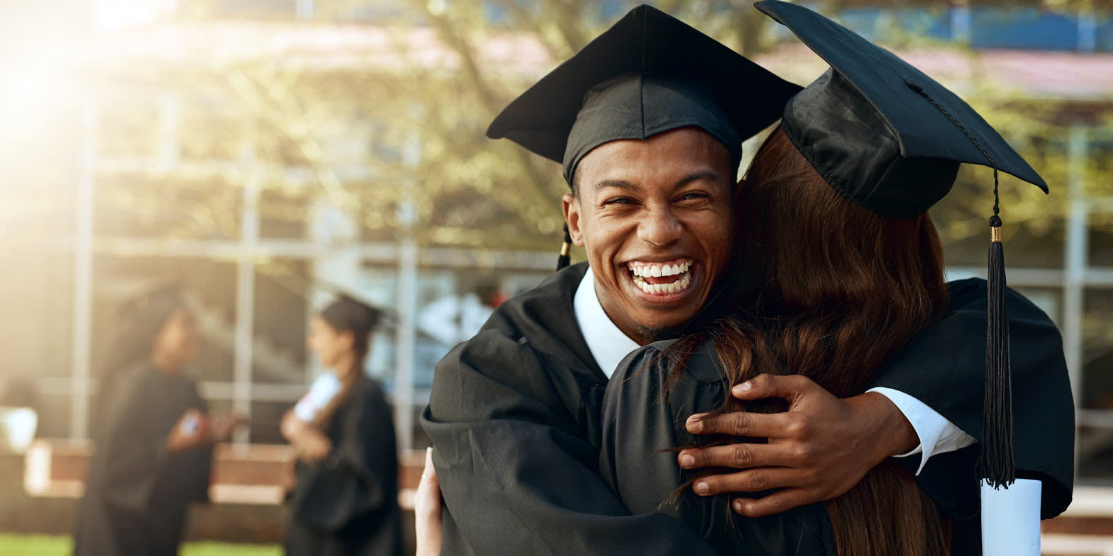 Young man wearing a graduation cap and gown hugging woman also wearing a cap and gown.