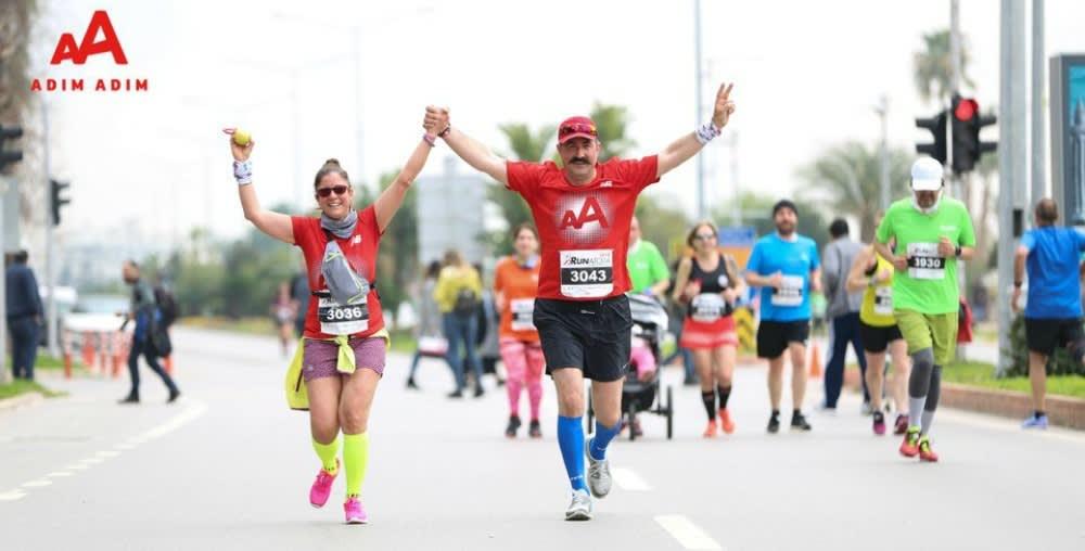 Adim Adim のシャツを着た 2 人のランナーが握り合った手を頭上に挙げて勝利のジェスチャーをしながら道を走っています。