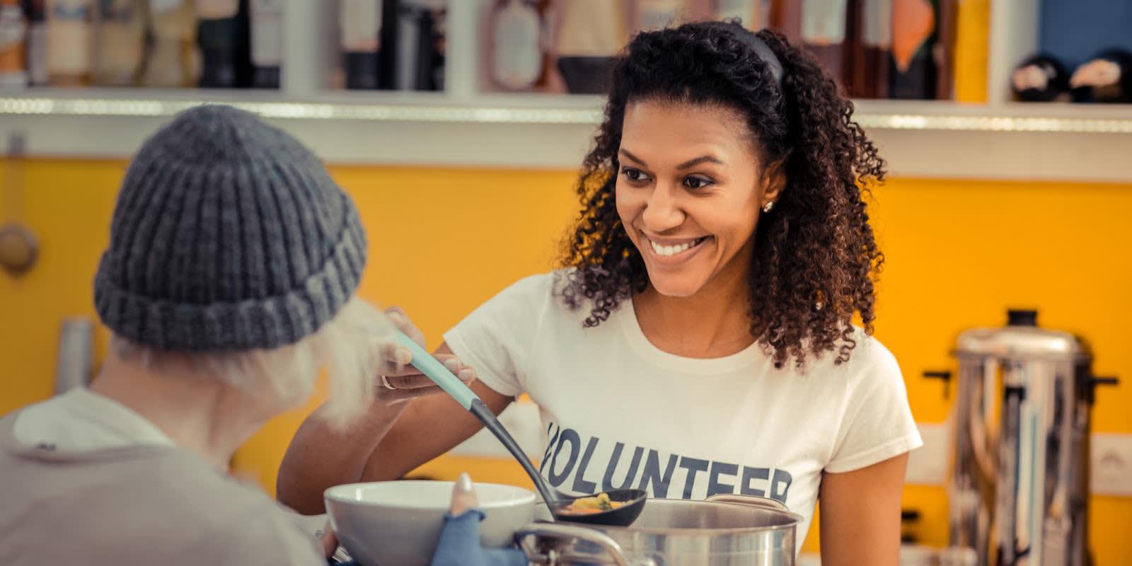 Uma mulher que se oferece para servir comida a um desabrigado.