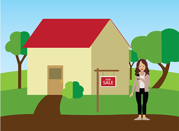 A broker who is looking at her phone while standing in front of a For Sale sign