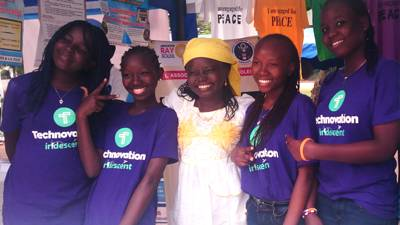 Four young women smiling wearing Technovation t-shirts, older woman smiling in the center, tshirts promoting peace hanging in the background.