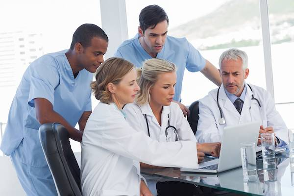 Doctors reviewing a file on a laptop