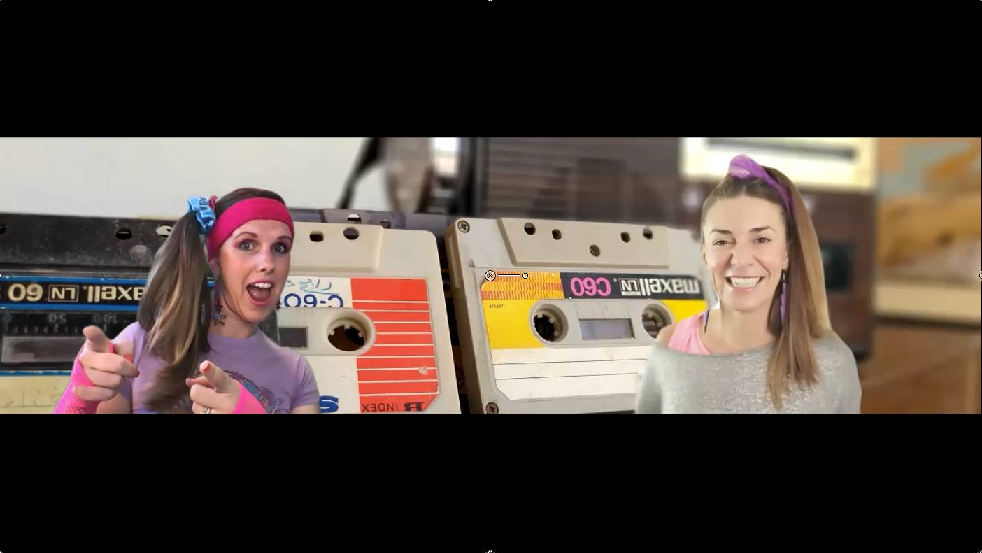 Two women dressed in 1980s athletic wear and sweatbands are pictured in split screen, with the woman on the left pointing both index fingers towards the camera.