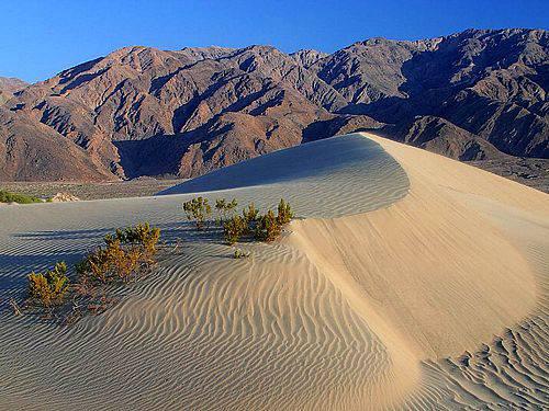 Uma foto das dunas de areia do Vale da Morte com montanhas ao fundo.