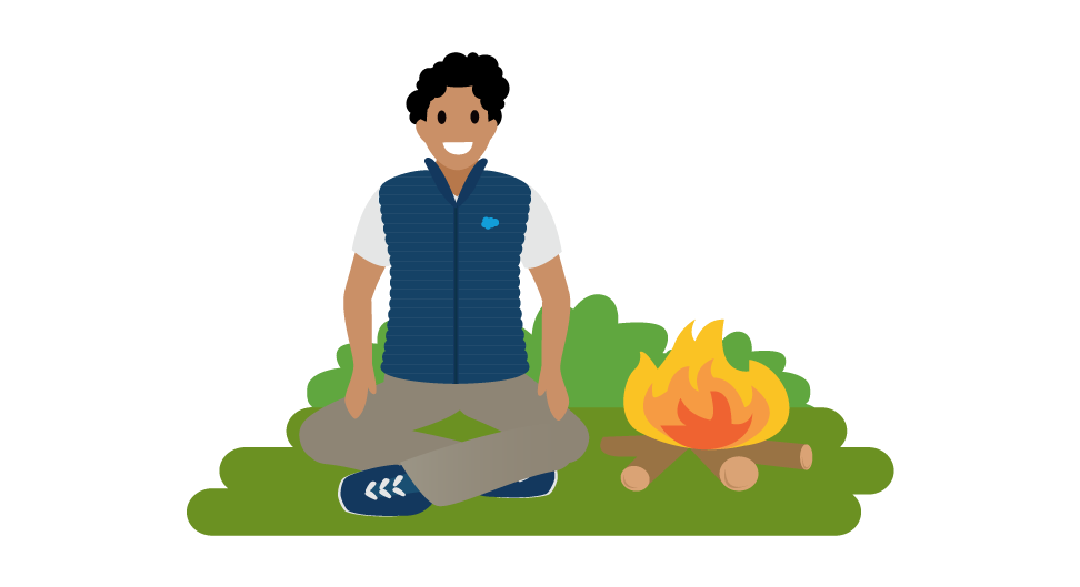 Image of an employee sitting by a campfire.