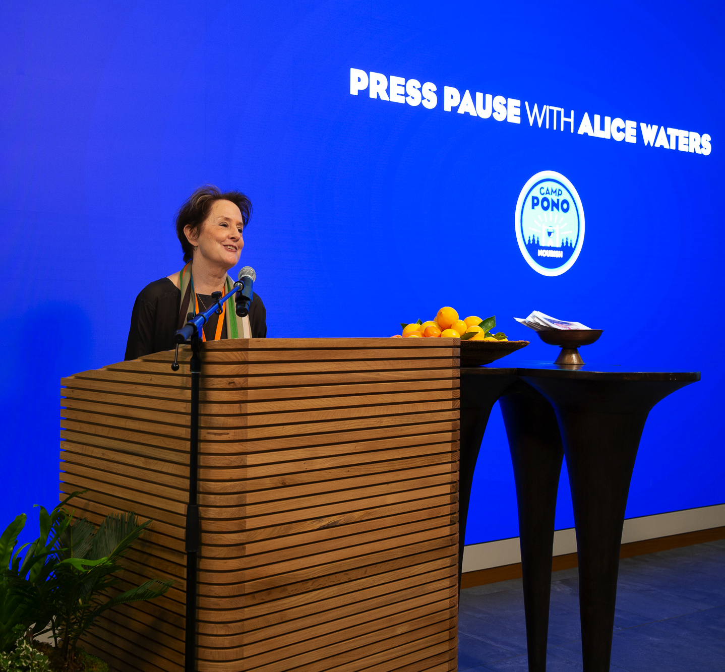 """An image of Alice Waters speaking at Salesforce with """"Press Pause with Alice Waters"""" displayed on a screen in the background."""