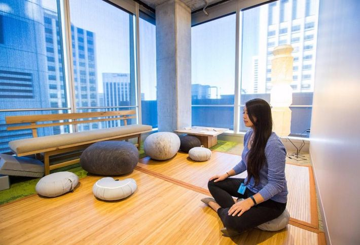 Image of a Salesforce meditation zone with a person sitting cross-legged on the hardwood floor meditating.