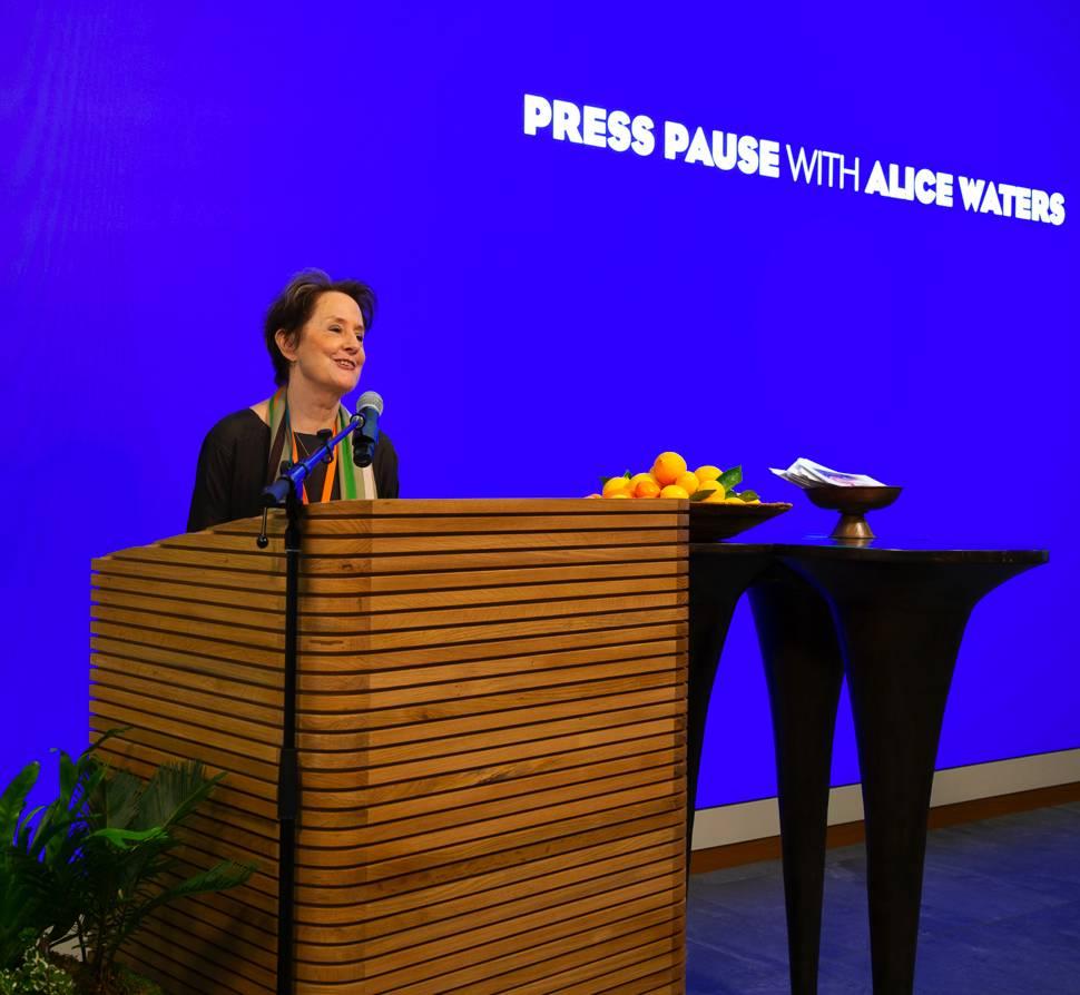Une photo d'AliceWaters lors de son intervention chez Salesforce, avec la phrase «Appuyez sur pause avec Alice Waters» affichée sur un écran en arrière-plan.