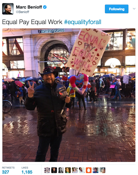 Salesforce CEO Marc Benioff holds a sign at the local women's march in 2017.