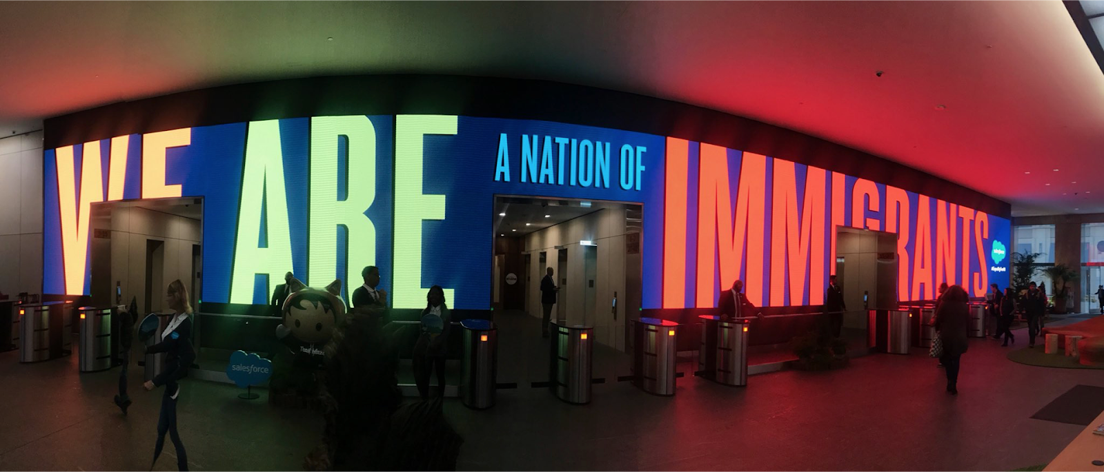 """Lobby of a Salesforce building with the quote """"We are a nation of immigrants"""" as a light-up display in reaction to policies around DACA and H1B visas."""