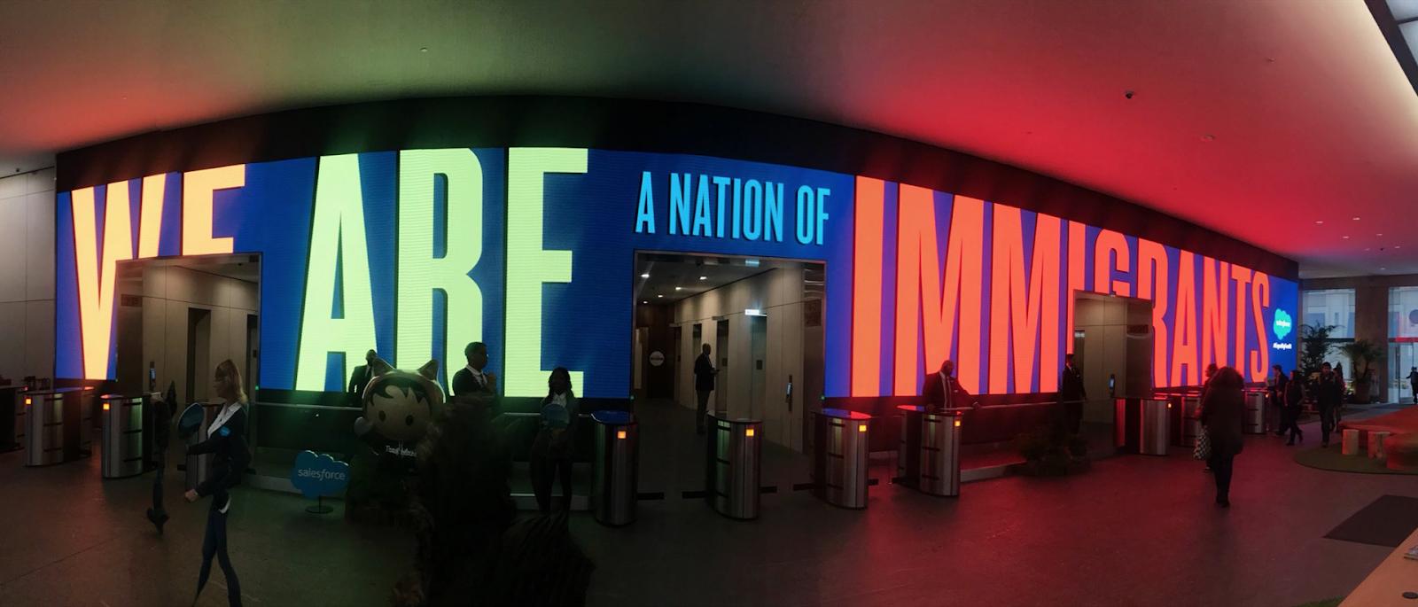 """Recepción de un edificio de Salesforce con la cita """"Somos una nación de inmigrantes"""" como pancarta encendida en reacción a las políticas sobre DACA y los visados H1B."""