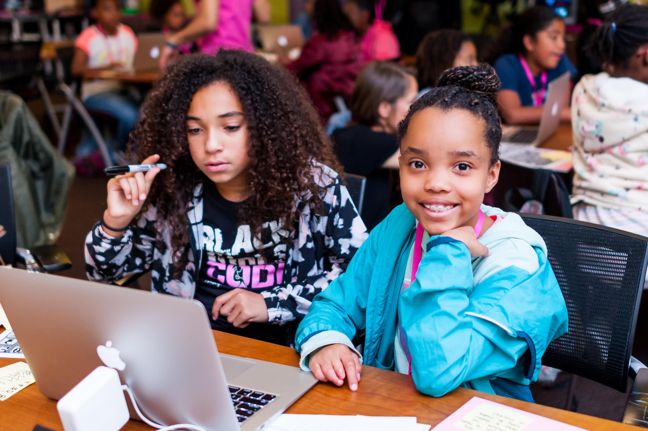 コンピュータの前で勉強する 2 人の少女。