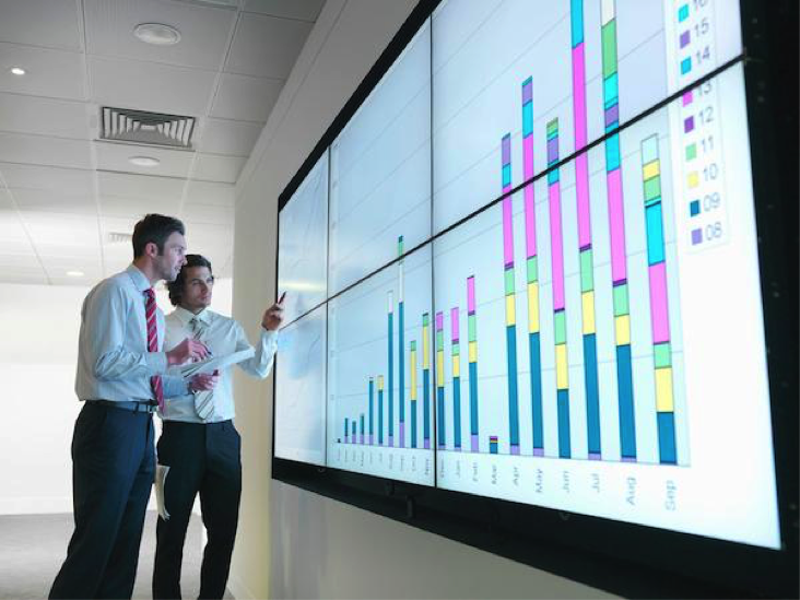 Two men in front of a video screen displaying a chart
