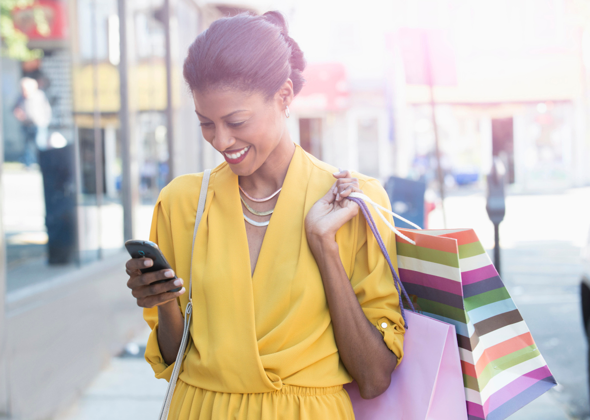 Photograph of a smiling woman on a city street. She is looking at her phone and carrying two shopping bags.