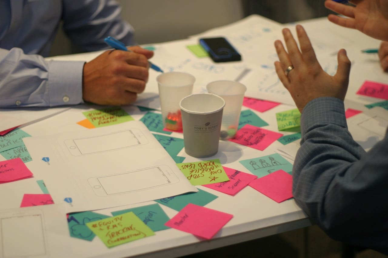 Photo of work table, showing cups, papers, post-its, and hands gesturing.