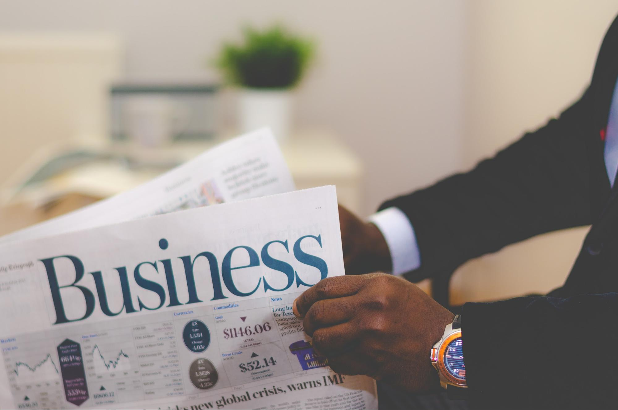 Phone close up of hands holding a business newspaper