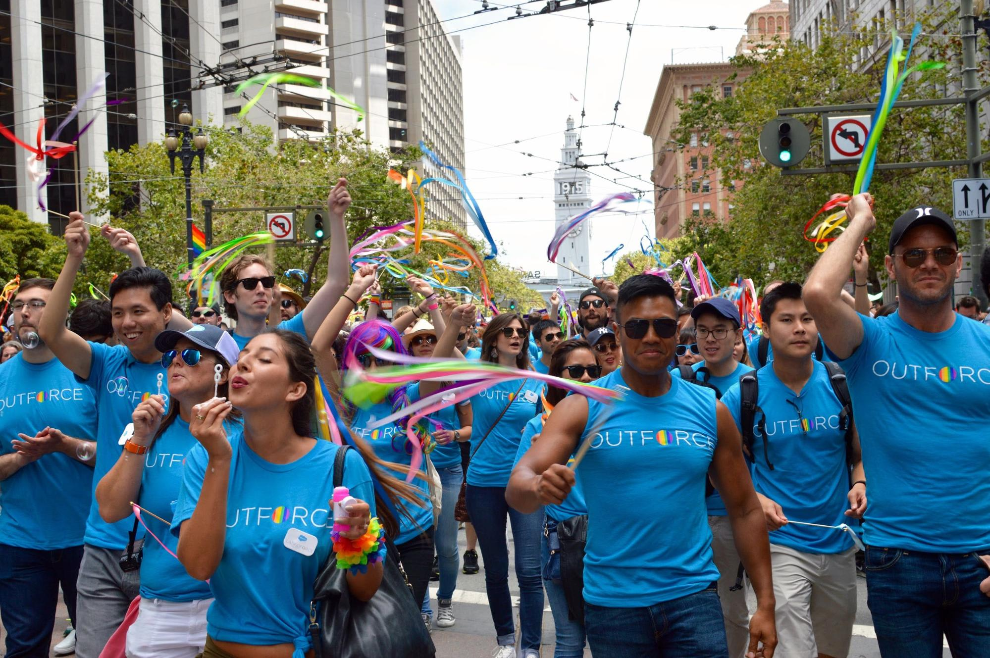 Picture of a Pride parade, with people marching in Outforce tshirts, blowing bubbles, and waving streamers