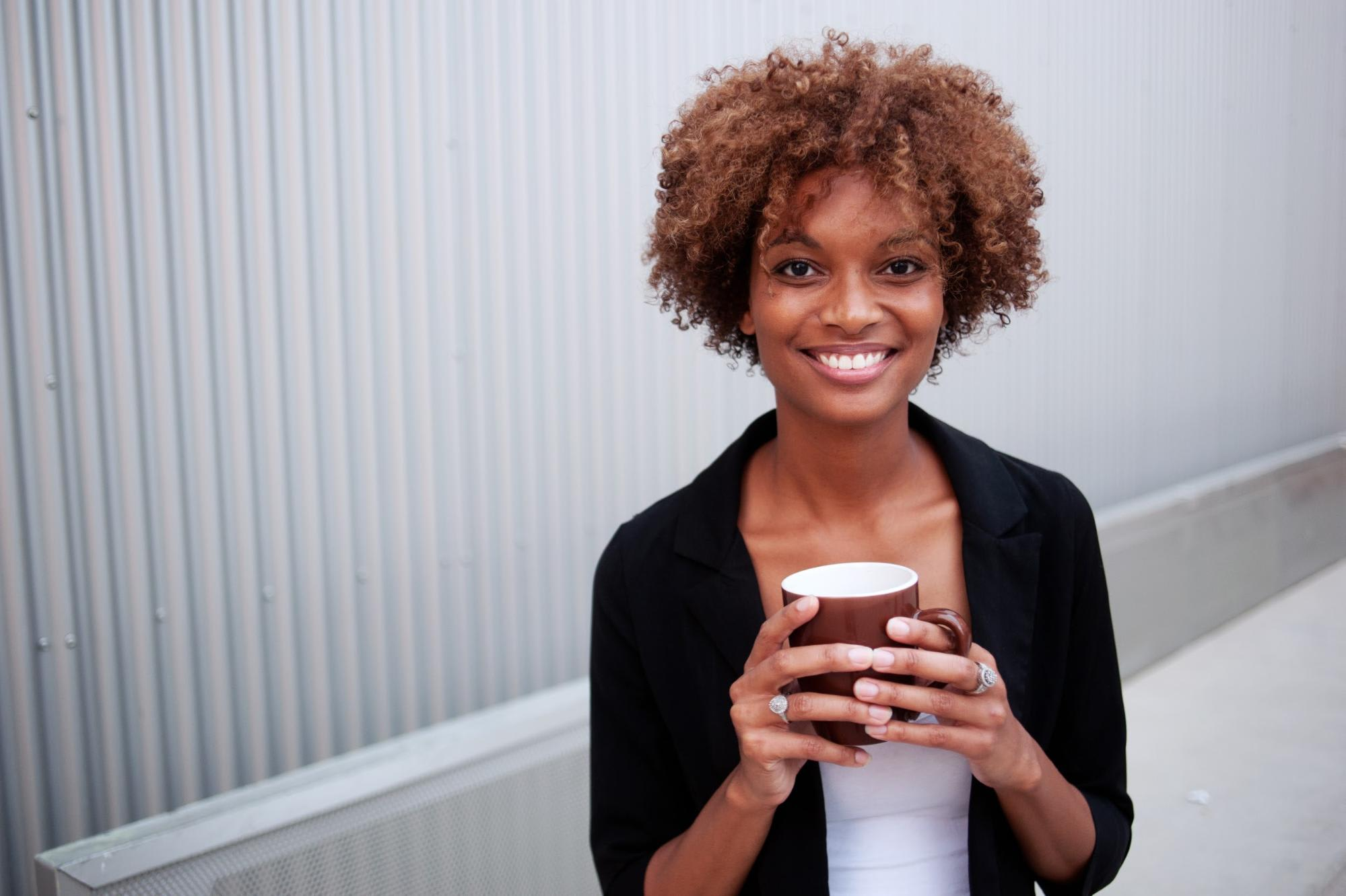 Person smiling, holding a coffee cup