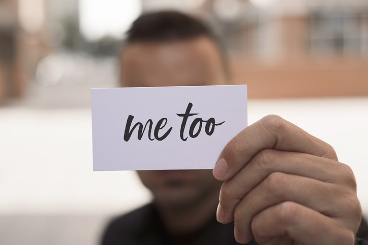 Man holding me too sign