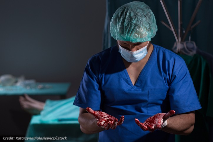 Image of a surgeon with blood on his hands
