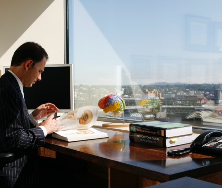 Dr. Aaron DeShaw at desk with book