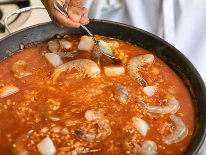 chef hand stirring a large paella pan
