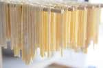fresh homemade fettuccine drying on a rack