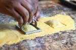 chef's hands stamping ravioli with a ravioli press